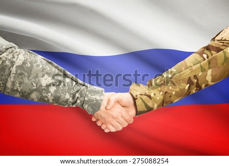 Soldiers shaking hands with flag on background - Russia - stock photo