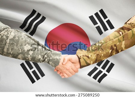Soldiers shaking hands with flag on background - South Korea - stock photo