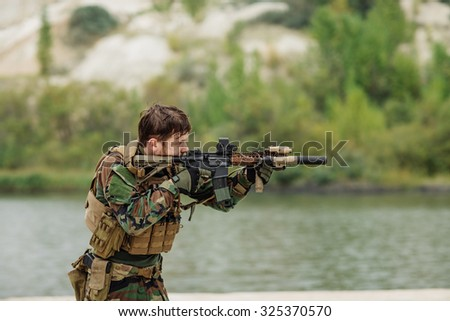 soldiers to aim and shoot at a target with automatic weapons - stock photo
