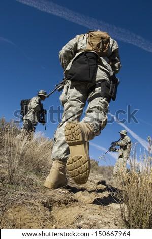 Soldiers walking in field - stock photo