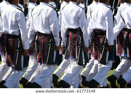 Soldiers wearing parade army wear.  They are marching at a formal ceremony.  These uniforms are white with a patterned wrap around on the waist.  Celebrations of the Sultan of Brunei's birthday.