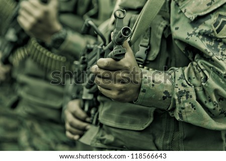 soldiers with assault rifle and camo suit