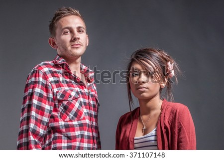 Solemn mixed race young couple look at camera