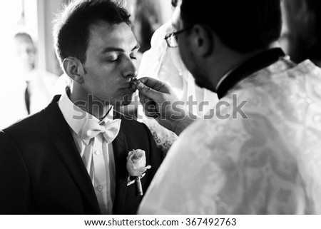 Solemn moment of marriage newlyweds in the church. Groom with closed eyes kissing a wedding ring, which gives the priest