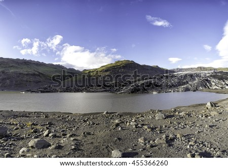 Solheimajokull outlet glacier in southern Iceland, blue sky and a lagoon has formed in front of it - stock photo
