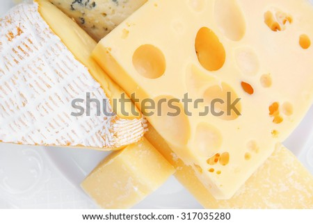 solid french cheese parmesan brie and edam on white platter isolated on white background
