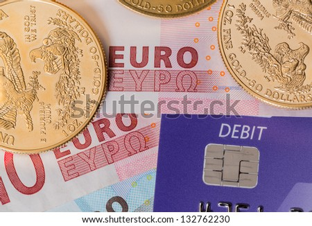 Solid gold coins contrasted with debit word on plastic card on euro note suggesting debt problems - stock photo