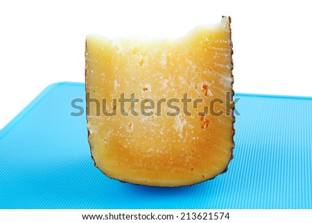 solid yellow parmesan on blue plastic board - stock photo