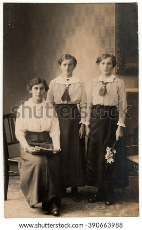 SOLINGEN, GERMANY - CIRCA 1920s: Vintage photo shows three women pose for photohrapher. Black & white photo with sepia tint.