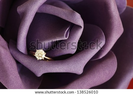 Solitaire engagement diamond ring (ideal cut) encrusted on 18K gold ring embedded in purple rose. - stock photo