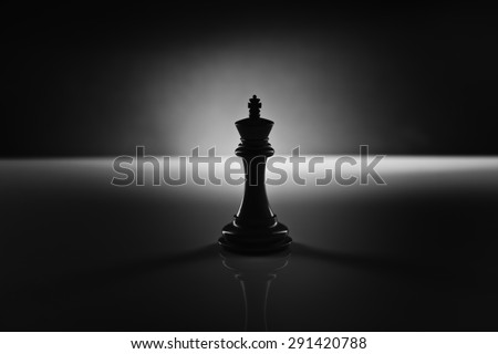 Solitary black chess king carved in genuine ebony wood in focus standing on a glossy table in the dark