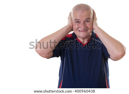 Solitary elderly man wearing short sleeved blue shirt cringes and covers ears with both hands
