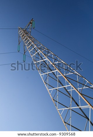 Solitary electricity power-line tower against a blue sky
