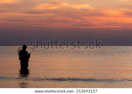 Solitary fisherman waiting for the next catch with the faded sun hovering on the horizon.