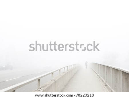 Solitary man in distance walks away, disappearing into the fog. Pedestrian walkway on bridge recedes toward subject at vanishing point. High key, desaturated, horizontal with copy space. - stock photo