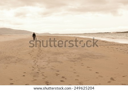 Solitary man taken from behind walking in an empty beach.Footprints on the sand. - stock photo