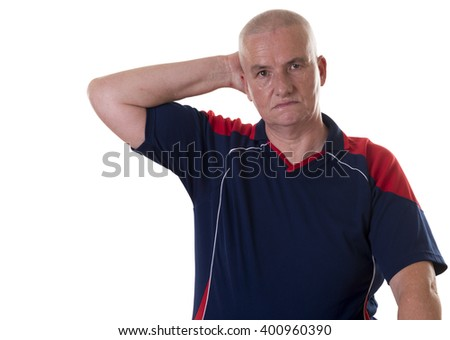 Solitary man wearing bowling shirt holding one hand to his ear on white background