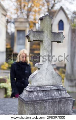 Solitary woman mourning by gravestone, remembering dead relatives in on Pere Lachaise cemetery in Paris, France. - stock photo