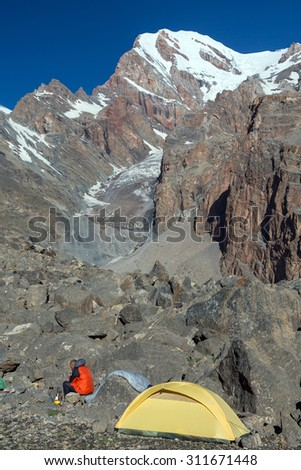 Solo Alpine Climber Camp at Morning. Yellow Small Sole Tent Located on Rocky Moraine Mountain View on Background with Man Sitting on Stone and Cooking Breakfast Preparing to Ascent Vertical - stock photo