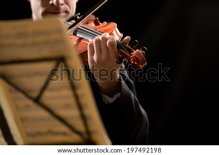 Solo violin player with sheet music and stand on foreground. - stock photo
