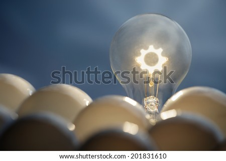 Solution and communication business concepts. Idea symbol, light bulb, gear inside light blob. - stock photo