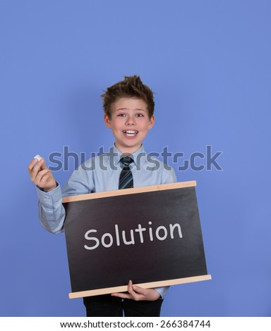 Solution concept. Boy with chalkboard slate on blue background. Solutions handwritten with white chalk on a blackboard. - stock photo
