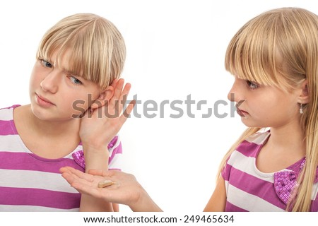 Solution for hearing problems - Girl offering a hearing aid to her girlfriend who can't hear well. Studio isolated on white. - stock photo
