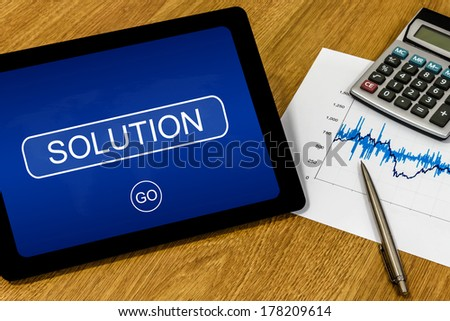 solution word on digital tablet with calculator and financial graph