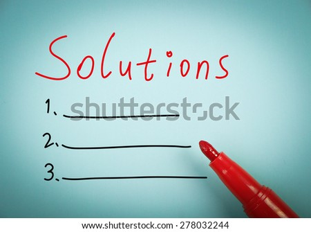 Solutions concept is on blue paper with a red marker aside. - stock photo
