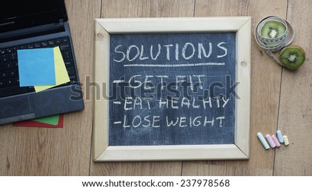 Solutions get, fit, eat healthy and lose weight written on a chalkboard at the office                           - stock photo