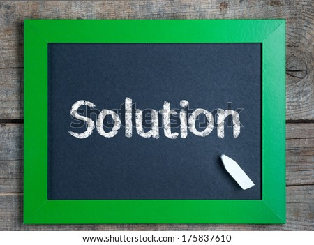 Solutions title word written on green framed chalkboard on wooden background  - stock photo
