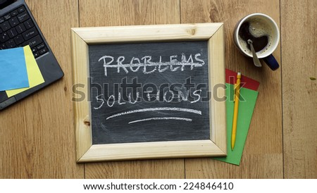 Solutions written on a chalkboard at the office - stock photo