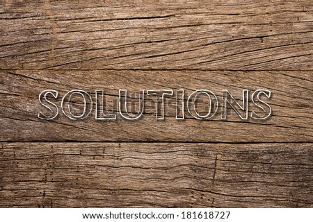 Solutions written on wooden background