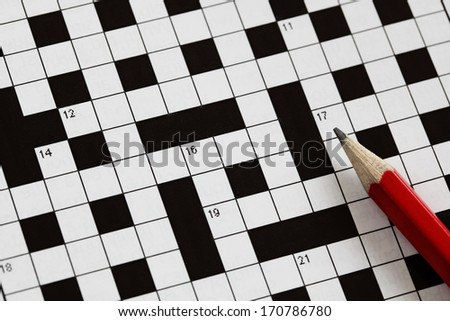 Solving a crossword puzzle with red pencil - stock photo