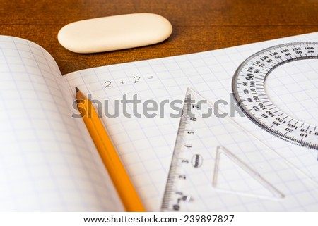 Solving mathematical problems, a notebook with drawing tools on the table