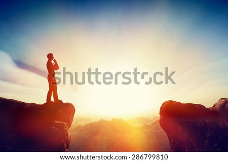 Solving the problem, thinking about solution, challenge concept. Man standing on mountain think about getting on the other side. Sunset sky, light. - stock photo