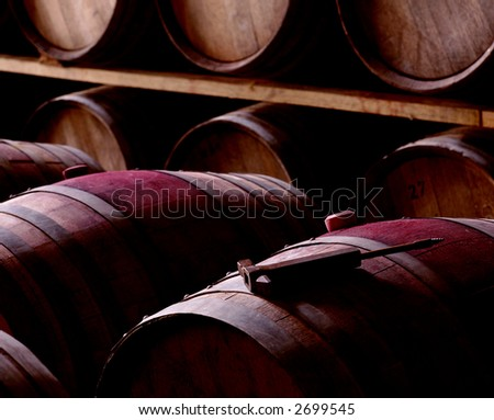 some barrels in a winery, one of them with some tool over it