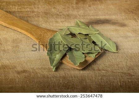 Some bay leaves in wooden spoon over wood background - stock photo