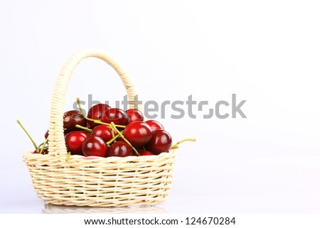 Some beautiful sweet cherry fruit in a basket isolated on white background