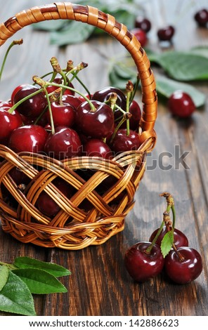 Some beautiful sweet cherry in a basket  on a wooden background