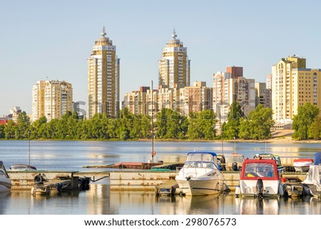 Some boats are parked on the Dnieper River in Kiev, Ukraine. High buildings of the city appears in the background.
