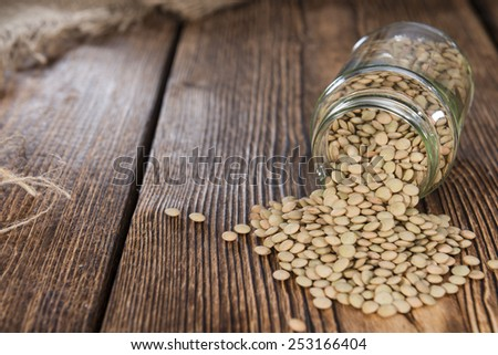 Some brown Lentils (close-up shot) on wooden background  - stock photo