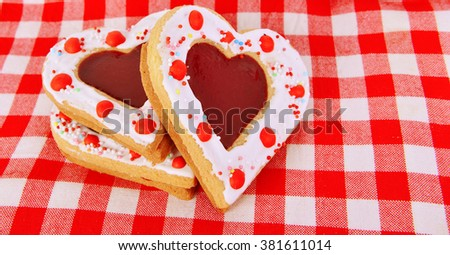 Some butter shortbread cookies heart  stuffed with shaped jelly on the bright  on the red table cloth. Romantic treat concept. - stock photo