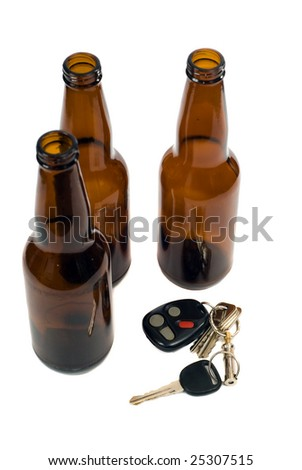 Some car keys shot alongside some empty beer bottles, isolated against a white background - stock photo