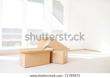some cardboard boxes in an empty room - stock photo