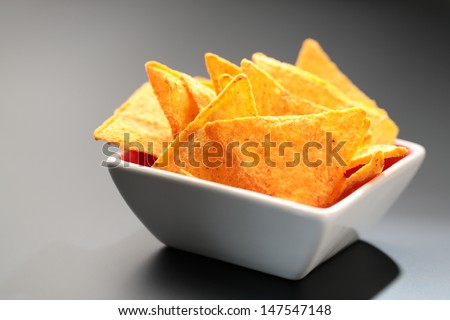 Some cheese flavored tortilla/Nacho chips in a bowl on dark background. - stock photo