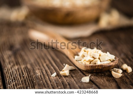 Some chopped Peanuts (close-up shot; selective focus) on wooden background - stock photo