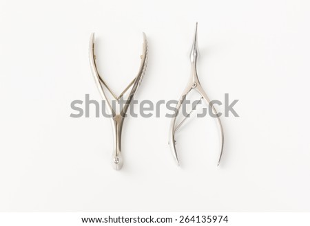 some chromeplated medical surgical tools lie on a white background - stock photo