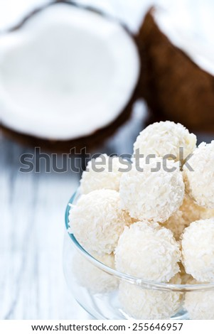 Some Coconut Pralines (close-up shot) on wooden background