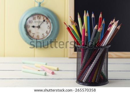 Some colored pencil and chalks on a white wooden table. In the background a turquoise clock and a blackboard on a yellow wainscot. Vintage - stock photo